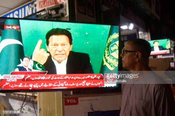 Bystander listens Pakistan's Prime Minister Imran Khan addressing the nation on television, in Karachi on March 4 after Foreign Minister Shah Mahmood...