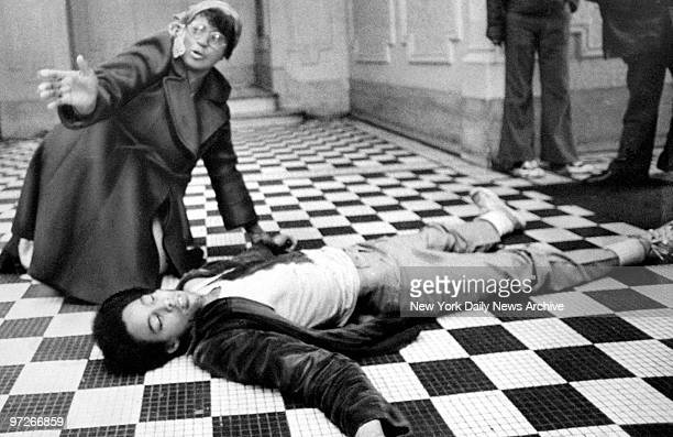 Bystander Lois Hicks seeks help for Daryl Brian as he lies in the hallway of an apartment building on Sterling St after being stabbed by a girl...