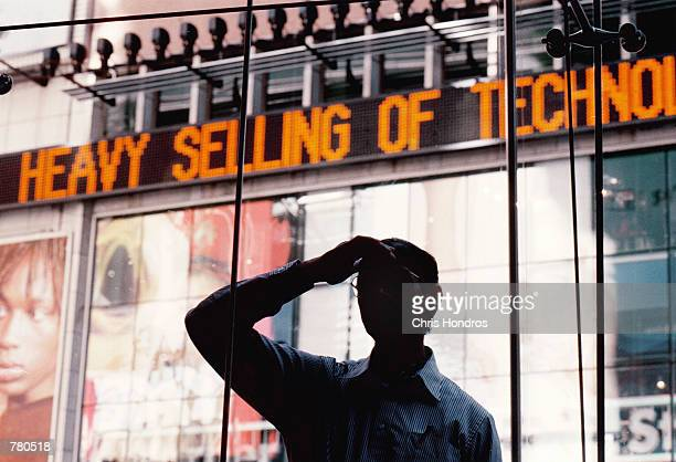 A bystander looks into the window of the Nasdaq MarketSite near the close of trading April 12 2000 in New York City The Nasdaq lost 28669 points to...