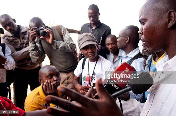 Bystander Peter Ndegwa is interviewed by journalists after two improvised explosive devices went off in Gikomba market on May 16 2014 in Nairobi...