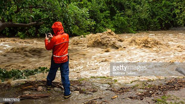 Bystander snaps a picture of the raging waters flowing down Boulder Creek during the 2013 Colorado floods.