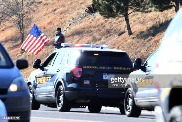 Bystander stands on the side of the road on S. Broadway holding an American flag as a procession leaves Littleton Hospital with fallen officer who...