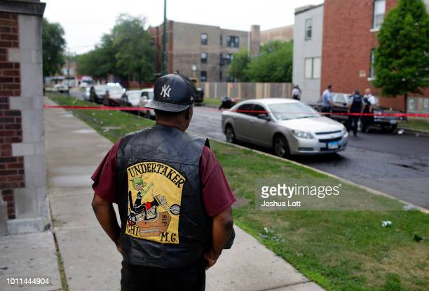 A bystander watches as Chicago Police officers and detectives investigate a shooting where multiple people were shot on Sunday August 5 2018 in...