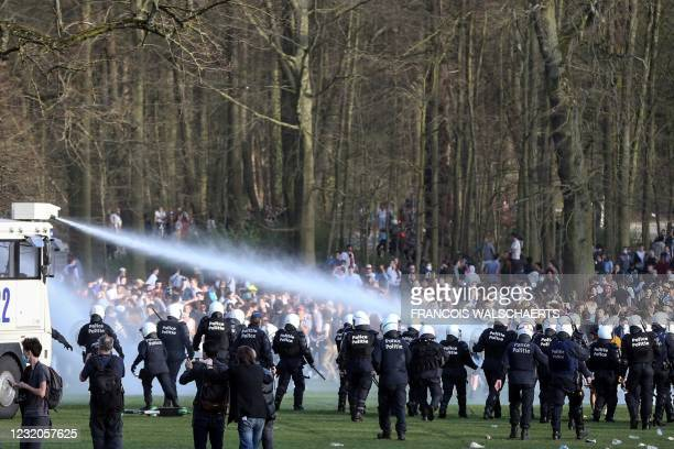 Bystanders and demonstrators are soaked by a Belgian police water canon as police officers surround them at the Bois de la Cambre parc, in Brussels,...