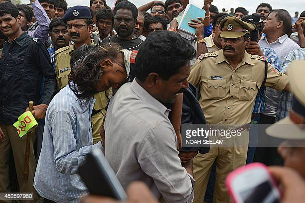 Bystanders and Indian police look on as a father carries the body of her daughter towards an ambulance at the site of the collision between a school...