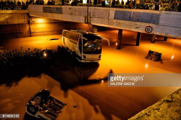 TOPSHOT Bystanders and rescue personnel look at vehicles submerged in floodwaters on a highway near Eleusina southwest of Athens on November 15 after...