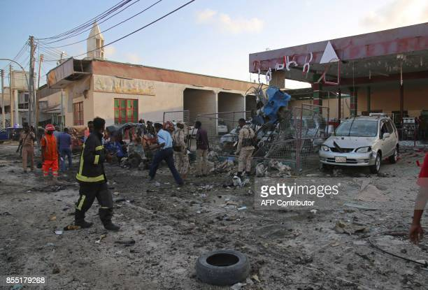 Bystanders and rescue workers look at the wreckage of a rickshaw and other vehicles after a car bomb exploded in the centre of Mogadishu on September...