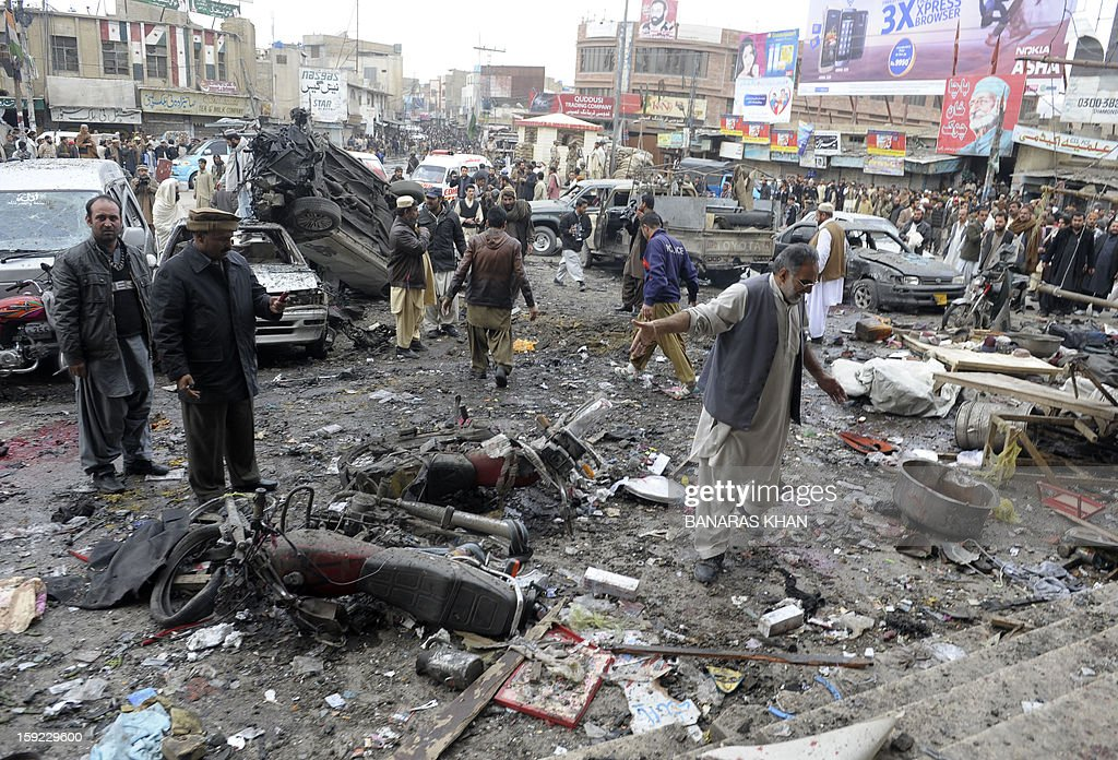 Bystanders are pictured at the site of a bomb explosion in Quetta on January 10, 2013. A bomb attack killed 11 people and wounded dozens more in a crowded part of Pakistan's southwestern city of Quetta, police said. AFP PHOTO/Banaras KHAN
