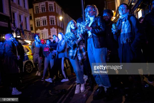 Bystanders finish their drinks as police officers arrest a man on Old Compton Street in Soho on April 16, 2021 in London, England. Pubs and...