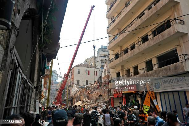 Bystanders gather as rescue workers dig through the rubble of a badly damaged building in Lebanon's capital Beirut in search of possible survivors...