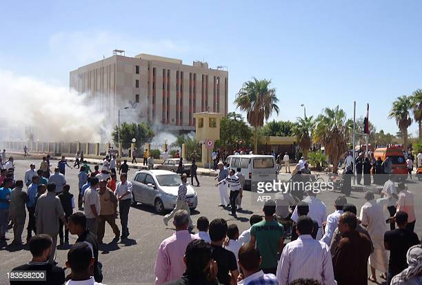 Bystanders gather at the scene as smoke rises from an Egyptian provincial police headquarters in alTur in the southern part of Egypt's Sinai...