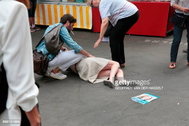 Bystanders give assistance after Les Republicains party candidate Nathalie Kosciusko-Morizet collapsed after an altercation with a passerby while...