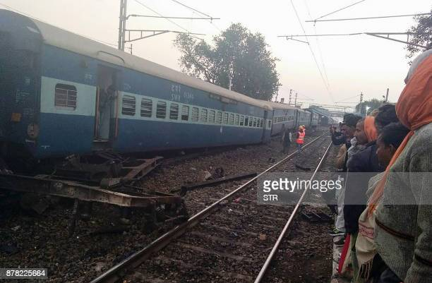 Bystanders look at the derailed carriages of a train near Manikpur railway station in northern India's Uttar Pradesh state on November 24 2017...