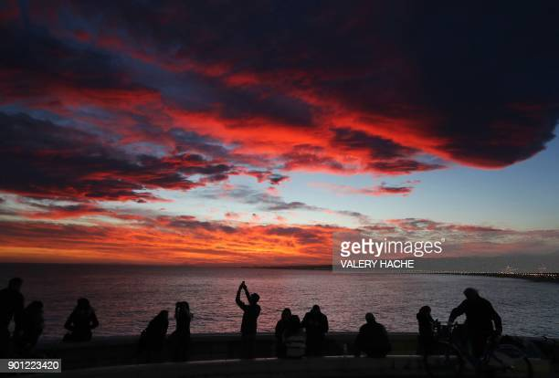 Bystanders look at the sunset on the 'Promenade des Anglais' Nice on January 4 after Storm Eleanor struck areas of France Winter storm Eleanor swept...