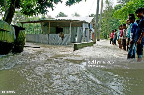 TOPSHOT Bystanders look on as floodwaters rage near a house in Kurigram northern Bangladesh on August 14 2017 Major rivers in Bangladesh are now...