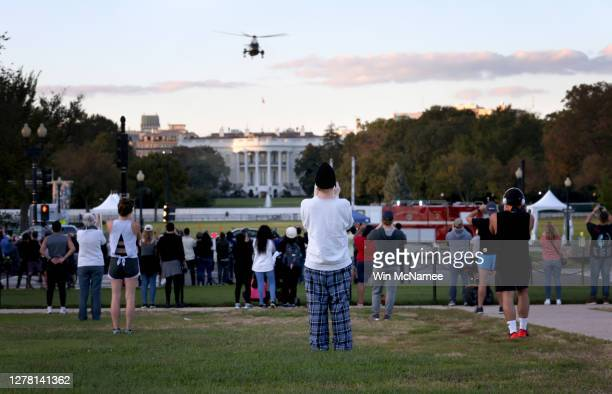 Bystanders look on as Marine One, the presidential helicopter, carries U.S. President Donald Trump from the White House to Walter Reed National...