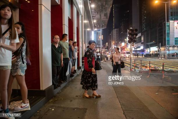 Bystanders look on as protesters clash with police during a prodemocracy march along Nathan Road in the Kowloon district in Hong Kong on October 20...