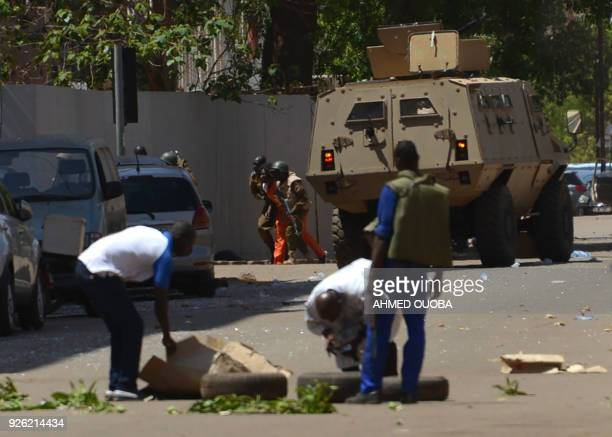 Bystanders look on as security personnel move beside an armoured personnel carrier in Ouagadougou on March 2 as the capital of Burkina Faso came...