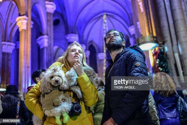 Bystanders look on during Christmas Mass at Saint Antuan Church in the Beyoglu district of Istanbul on December 24 2017 / AFP PHOTO / YASIN AKGUL