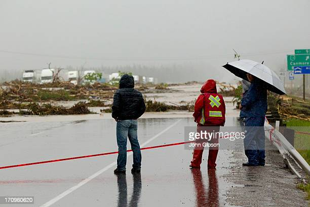 Bystanders look over debris deposited by Cougar Creek as it flowed up and over the TransCanada Hiway after it was closed June 20 2013 in Canmore...