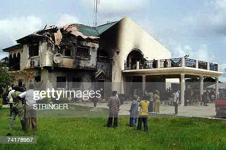 Bystanders looks at the private residence of vice-president elect Dr. Goodluck Jonathan destroyed by an unknown group of Niger Delta militias with dynamite 16 May, 2007 at Otuoke, Ogbia district in the oil rich Bayelsa State. The attackers also destroyed a nearby divisional police station killing a police inspector at the station.