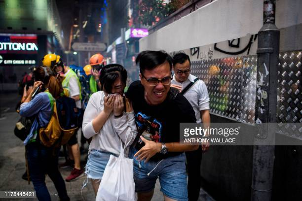 Bystanders react after police fired tear gas to disperse residents and protesters in the Mong Kok district of Kowloon in Hong Kong on October 27,...