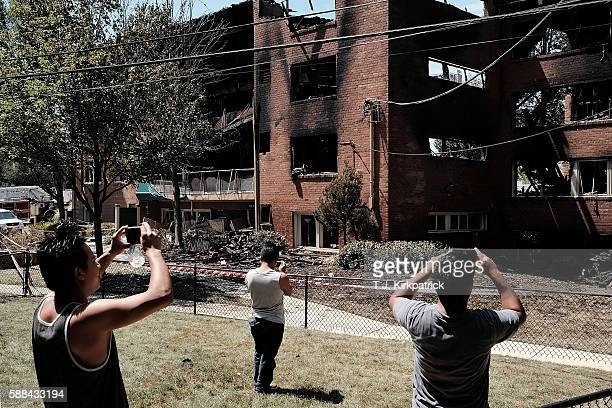 Bystanders take photos after an overnight explosion and fire destroyed an apartment building in the Flower Branch Apartments complex on August 11...