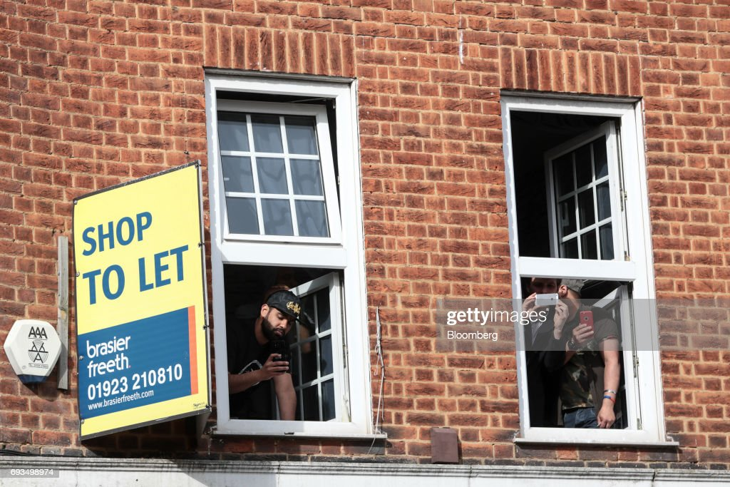 Bystanders take photos from a window as Jeremy Corbyn, leader of the U.K. opposition Labour Party, speaks during a general-election campaign rally in Watford, U.K., on Wednesday, June 7, 2017. The prime minister Theresa May and Corbyn, set out on whistle-stop tours of the country ahead of Thursday's vote, with polls all showing May's Conservatives ahead but disagreeing about whether the race is close.r. Photographer: Simon Dawson/Bloomberg via Getty Images