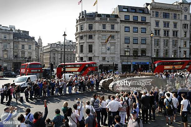 Bystanders watch and take pictures as a replica British Mark IV tank is driven on the road around Trafalgar Square in central London on September 15...