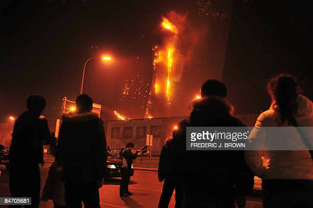 Bystanders watch as a spectacular fire engulfs a building being constructed about 500 metres north of the CCTV tower one of the icons of Beijing's...