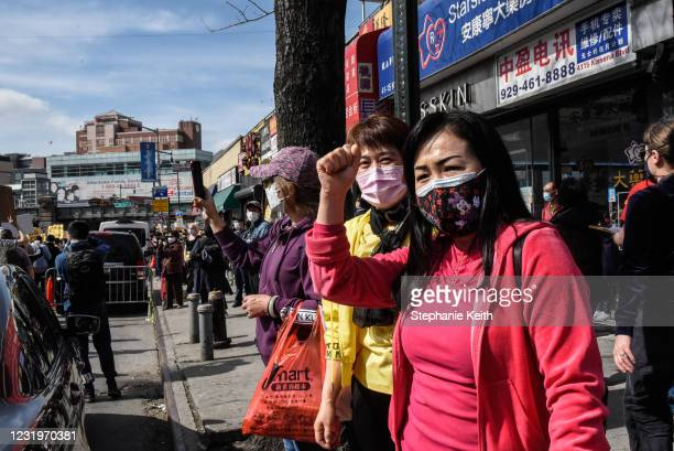 Bystanders watch as demonstrators march against anti-Asian violence through the streets on March 27, 2021 in the Flushing neighborhood in the Queens...
