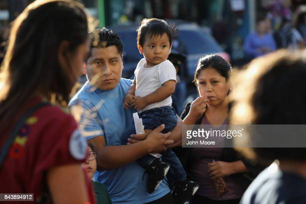 Bystanders watch as immigrants' rights demonstrators march in protest of President Trump's decision on DACA on September 7 2017 in the Queens borough...