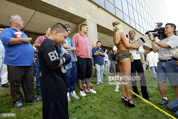 Bystanders watch as porn star Mary Carey talks to a reporter while gathering signatures for a run in the October 7 recall election of Gov Gray Davis...