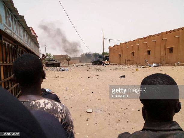 TOPSHOT Bystanders watch from afar the scene of an explosion in Gao northwestern Mali on July 1 2018 French soldiers operating in troubled northern...