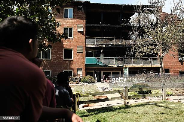 Bystanders watch the activity of fire and rescue crews and scene investigators after an overnight explosion and fire destroyed an apartment building...