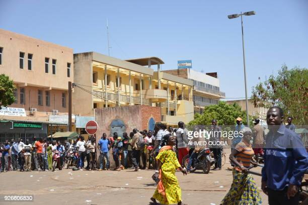 Bystanders watch the scene outside the headquarters of the country's defence forces in Ouagadougou on March 2, 2018 after dozens of people were...