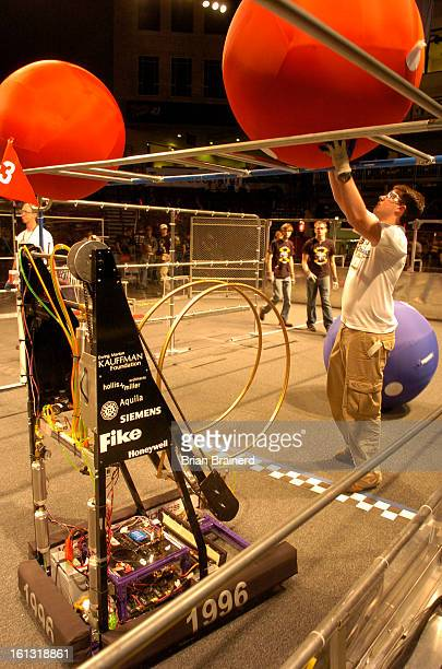bz28robots_bb_1 Judges place balls on an overhead rail to be knocked off by robots built by high school students who face off at University of Denver...