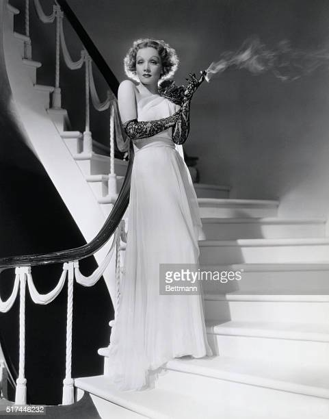 """Ca. 1935-ORIGINAL CAPTION READS: An ode to grace is offered by this white chiffon evening gown which Marlene Dietrich, Paramount star of """"The Devil..."""