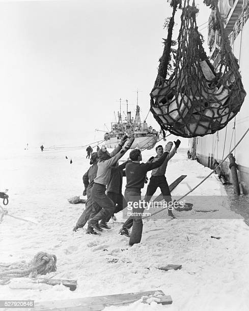 ca 1947 Workers get ready to unload food supplies from the USS Yancey onto the ice of the Bay of Whales The supplies are then transported by a...