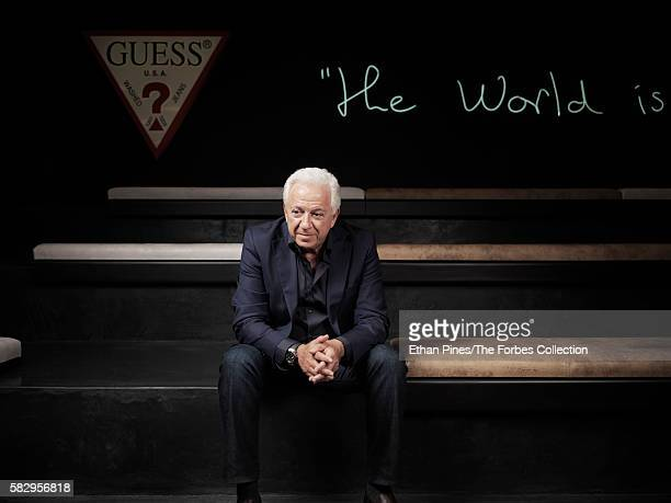 Guess cofounder Paul Marciano at the Guess headquarters in Los Angeles CA The neon sign says 'The world is our field' in Paul's handwriting