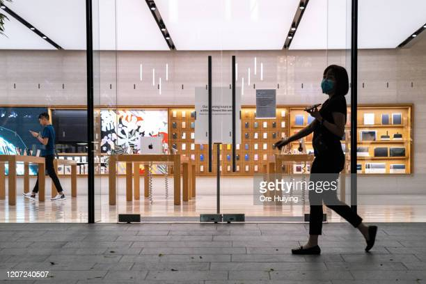 SINGAPORE SINGAPORE cA woman wearing a protective mask walk past an empty flagship Apple retail store on Orchard Road on March 15 2020 in Singapore...