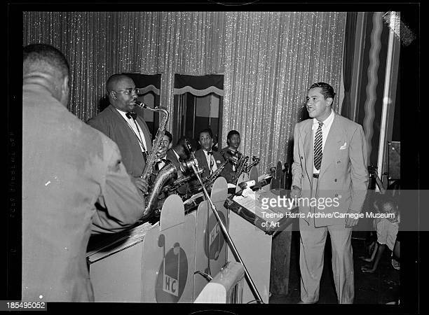 Cab Calloway conducting his orchestra including Milton Hinton on bass in foreground and Leon 'Chu' Berry on saxophone performing in Hill City...