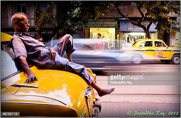 Cab driver in Kolkata looks on as he whiles away time relaxing on the machine that helps him earn his living.