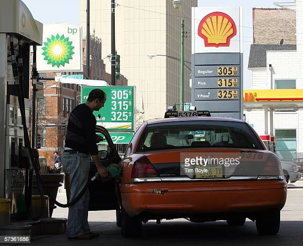 Cab driver pumps gas into his taxi at a BP Amoco station, next to a Shell station, April 18, 2006 in Chicago, Illinois. World oil prices hit a record...