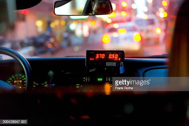 Cab meter on dashboard, view from car interior, night (focus on meter)