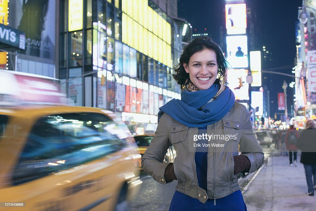 Cab passing woman in Times Square at night : ストックフォト