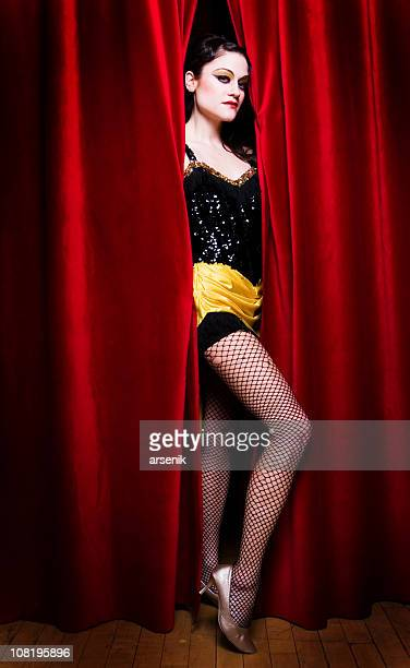 cabaret dancer standing between crack in curtains - cabaret stock photos and pictures