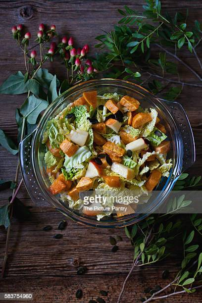 Cabbage, sweet potatoes and apple salad in a bowl on a rustic wooden table