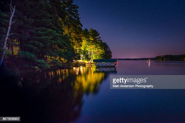 cabin at night on dam lake wi. - lake superior stock pictures, royalty-free photos & images