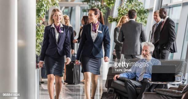 senhoras de tripulação de cabine andando pelo saguão do aeroporto - tripulação de bordo - fotografias e filmes do acervo